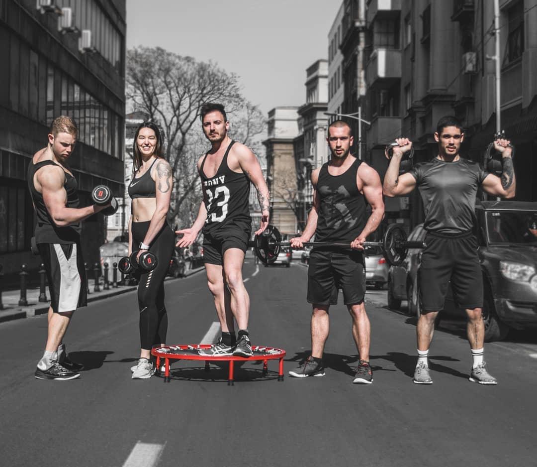 Slika trenera iz tema fit teretana sa optemom na ulici